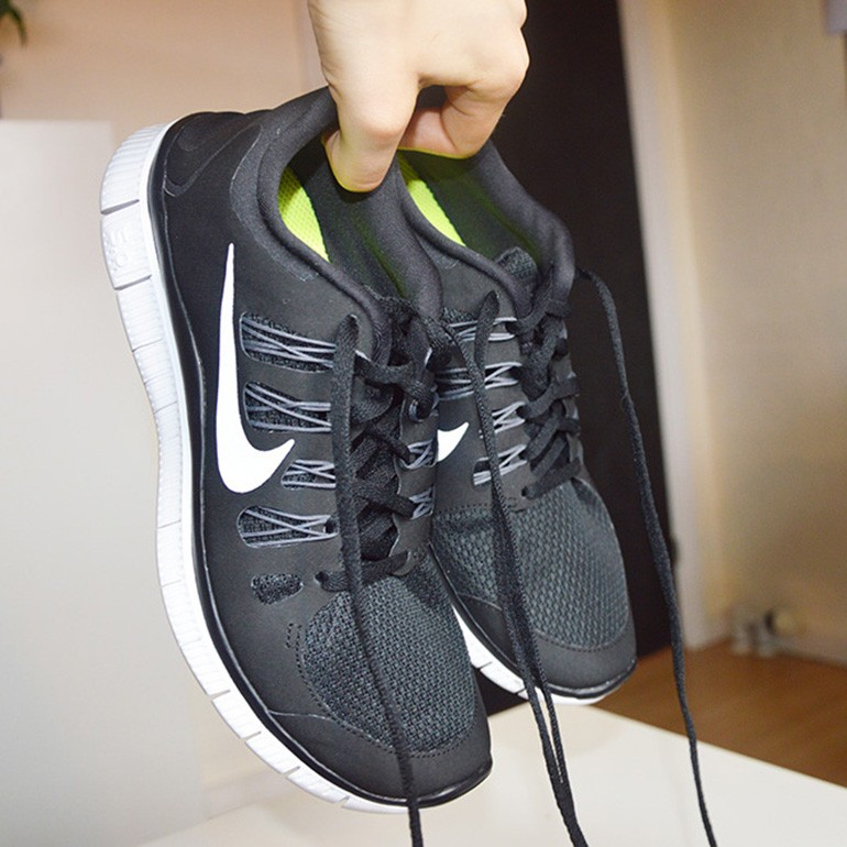 A pair Nike free air 5.0 black being held by a hand