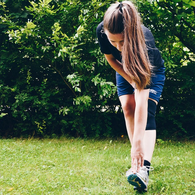 Image of girl in running shoes, stretching