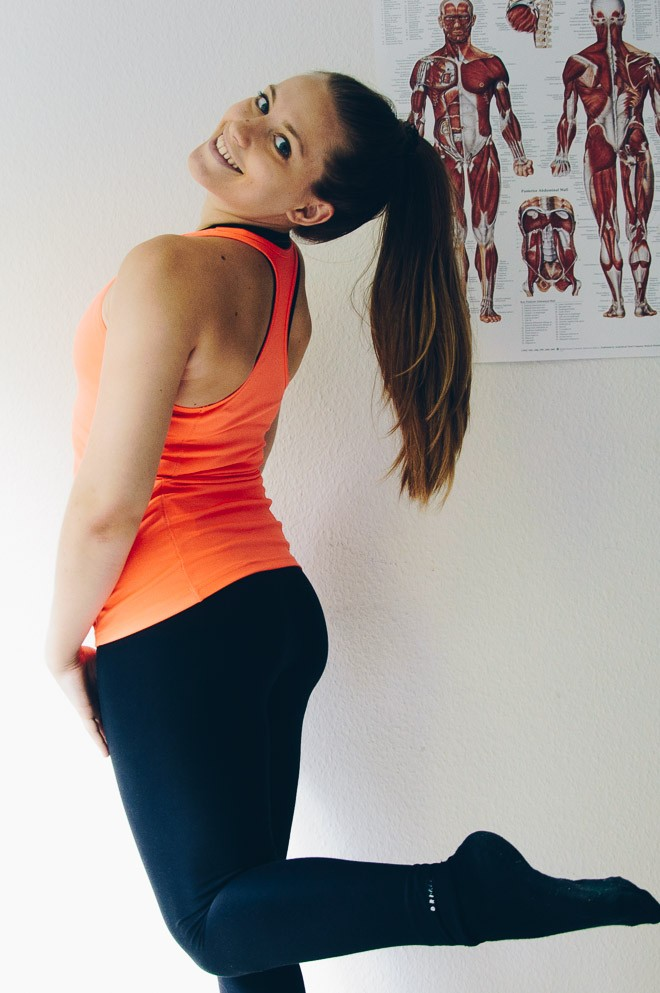 Anne in an orange workout top and black leggings