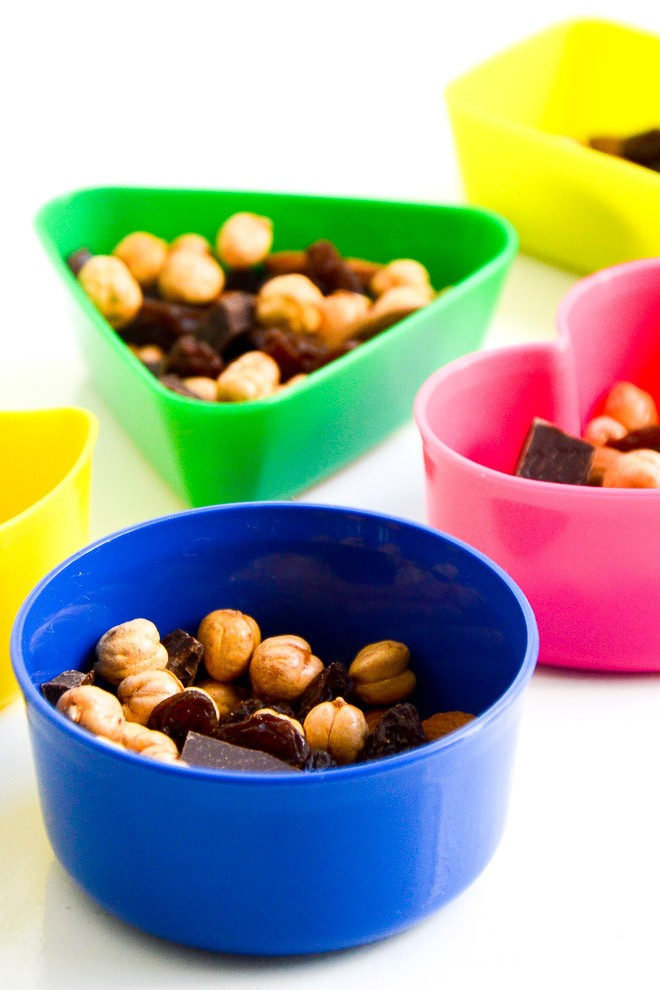 Trailmix in small containers containing almonds, roasted chickpeas, raisins and dark chocolate