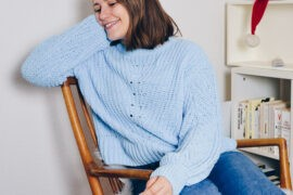 Anne sitting in her book corner in a rocking chair, wearing a cozy thick sweater and smiling