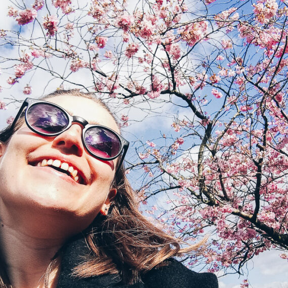 8 THINGS I WANT TO DO IN MAY - Anne smiling below a cherry tree blossoming