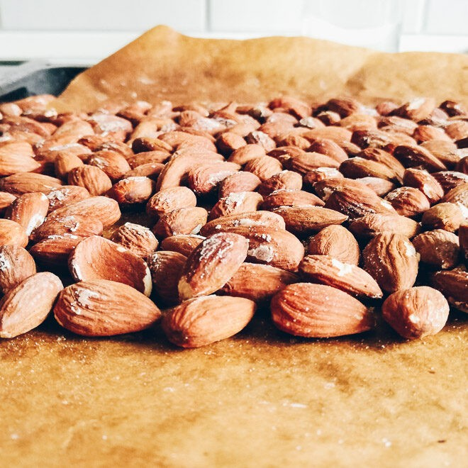 Salted almonds spread out on baking tray.